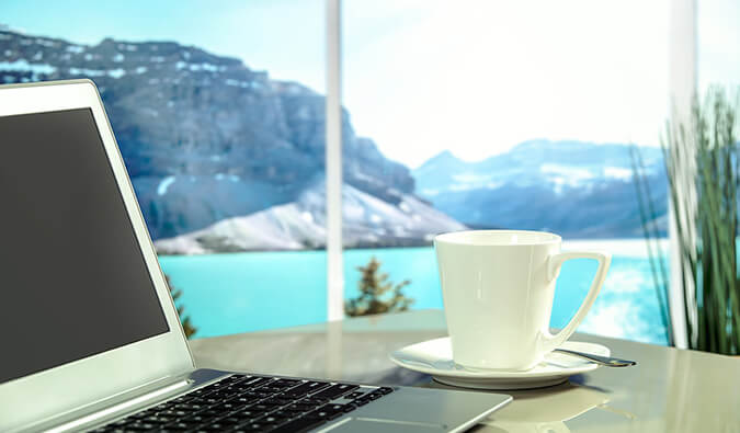 laptop and coffee cup and saucer on a table next to a window with a view of a lake and mountains in the background